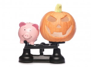 Piggybank and pumpkin on scales