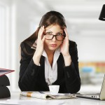A young businesswoman is looking stressed as she works at her computer